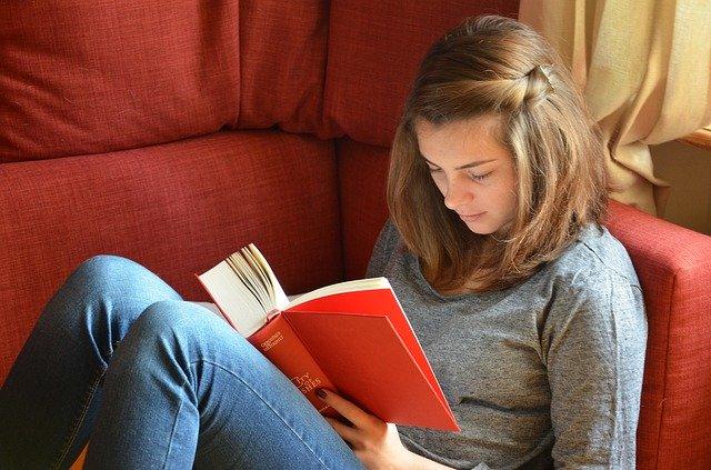 dívka při čtení knihy na nepohodlné pohovce